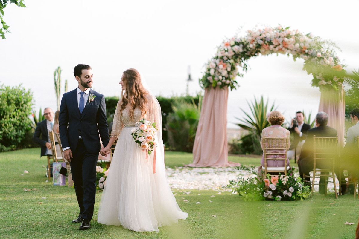 Couple and a Wedding Arch with flowers Tikitano Beach Marbella